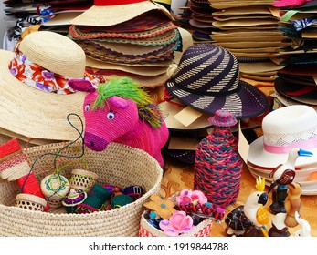 Colorful handmade souvenirs from straw - Panama Hats or Paja Toquilla hats or sombrero, baskets and toys at the traditional outdoor market in Cuenca, Ecuador. Popular souvenir from South America