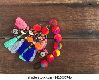 Colorful Handmade tribal fashion earring accessories made by woven thread Thai tradition style on old wood texture background