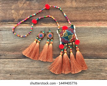 colorful handmade tribal fashion set necklace and earring embroidery woven thread Thai traditional fashion style old wood texture background