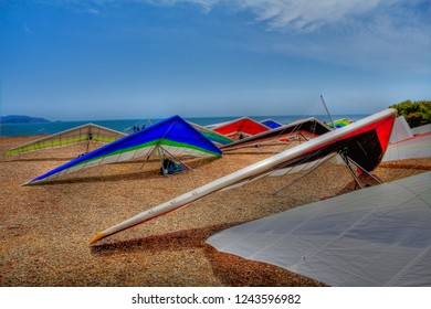 Colorful hang gliding wings lined up on top of a cliff at Fort Funston in San Francisco, one of the premier hang-gliding spots in the country
