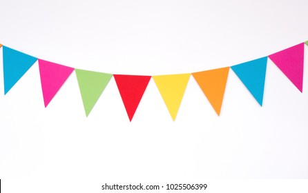 Colorful hanging paper flags on white wall background, decor items for party, festival, celebrate event