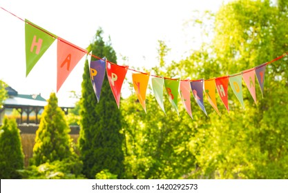 Colorful Happy Birthday bunting garland (banner) hanging outdoor - garden party decoration. Sunny summer or spring day, greenery as background.