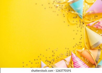 Colorful happy birthday or party background Flat Lay wtih birthday hats, confetti and ribbons on yellow background. Top View wit Copy space.