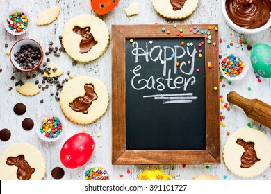 Colorful Happy Easter baking background. Cute idea for child sweets treats on holiday egg cookies sprinkling chocolate top view