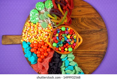 Colorful Happy Halloween trick or treat candy grazing platter charcuterie board with copy space.