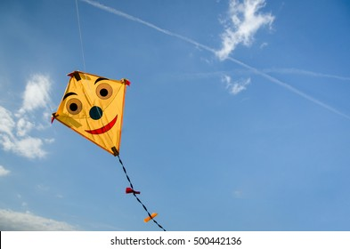 colorful happy smiling yellow kite flying high in blue sky