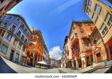 Colorful HDR image of European classical street with shops and apartments in Barbastro, Huesca, Spain on blue sky through fisheye lens