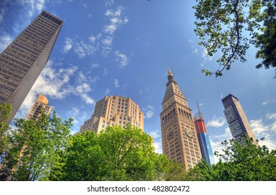 Colorful HDR image of the Manhattan skyscrapers through the trees in Madison Square Park on blue sky