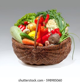 Colorful heap of vegetables in wicker basket on gray background