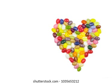 Colorful heart made of jelly beans on white background.