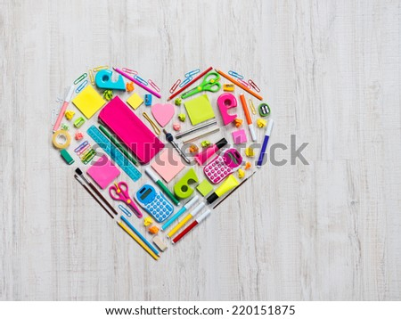 Colorful heart shape composed of stationery and office objects.