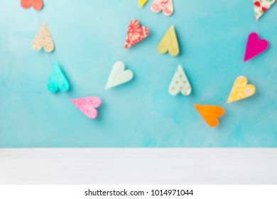 Colorful hearts garland decoration on blue background. Romantic concept. Copy space.