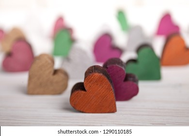 A colorful hearts on white wooden background