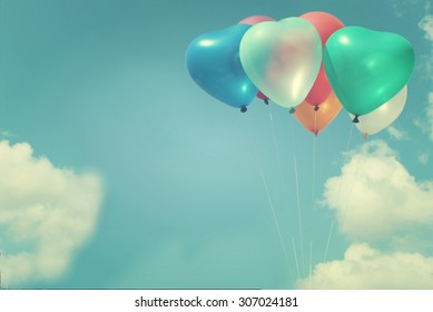 The colorful heart-shaped balloons flying blue sky background in vintage style, concept of love in summer and valentine, wedding