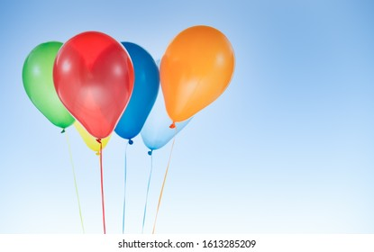 Colorful helium balloons for birthday and celebrations isolated at blue sky with copy space for free text
