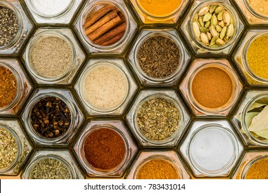 Colorful herbs and spices in hexagonal glass jars. Natural colors and top view. Horizontal picture.