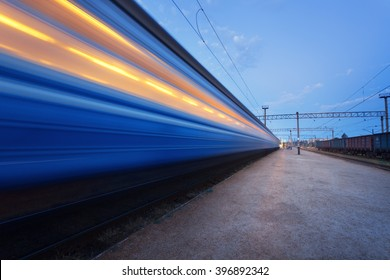 Colorful high speed passenger train on tracks in motion at rural railway station at sunset