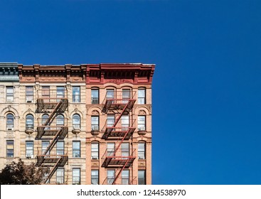 Colorful historic buildings on 4th Street in the East Village of Manhattan in New York City with empty blue sky background
