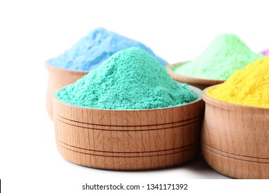 Colorful holi powder in bowls on white background