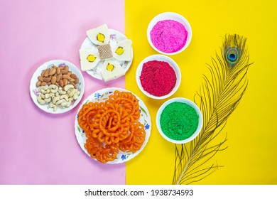 Colorful holi powder or gulal in ceramic bowl along with traditional Indian sweet food imarti, sandesh, cashew and almonds in plate on multicolor background. Happy holi, holi concept.