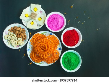 Colorful holi powder or gulal in ceramic bowl along with traditional Indian sweet food imarti, sandesh, cashew and almonds in plate on black background. Happy holi, holi concept.