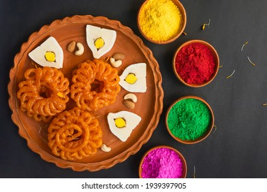 Colorful holi powder or gulal in earthen bowl along with traditional Indian sweet food imarti, sandesh, cashew and almonds in plate on black background. Happy holi, holi concept.