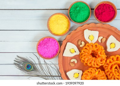 Colorful holi powder or gulal in earthen bowl along with traditional Indian sweet food imarti, sandesh, cashew and almonds in plate on wood background. Happy holi, holi concept.