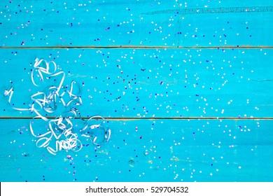 Colorful holiday confetti and ribbon border on blank antique rustic teal blue textured wood background sign; color copy space for text with pink, purple, blue decorations
