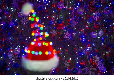 Colorful holiday lights glow on a Santa hat in front of a twinkling Christmas tree background