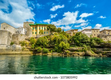 Colorful home surrounded by older stone buildings on the shore of the Neretva River near the old bridge in Mostar Bosnia and Herzegovina