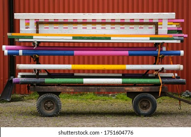 Colorful horse jumping equipment on an old trolley.