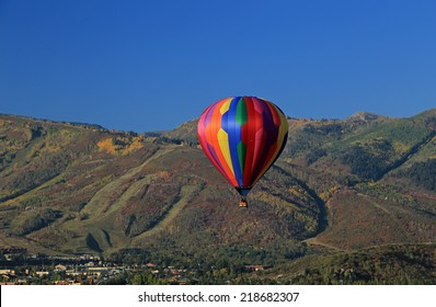 Colorful hot air balloon with autumn colors in the mountains above Park City, Utah, USA.