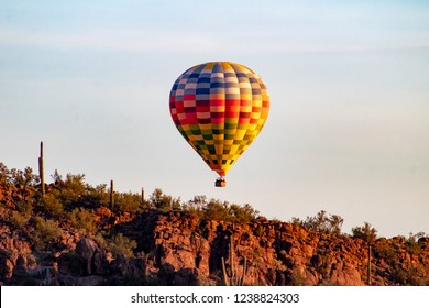 A colorful Hot Air Balloon floating over the Sonoran Desert near dawn in the early morning sky. Beautiful Southwestern landscape, saguaro cactus, mountains, white wispy clouds. Tucson, Arizona. 2018.