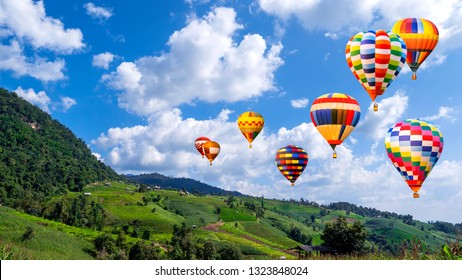 Colorful hot air balloon fly over beautiful landscape of green paddy field / rice field fram at countryside in Chiangmai, Thailand