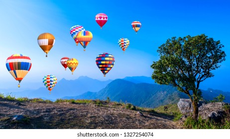 Colorful hot air balloon fly over mountain and big tree under blue sky at Chiangrai, Thailand