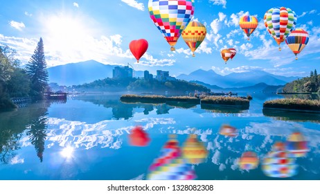 Colorful hot air balloon fly over beautiful landscape view of mountain and lake with reflection in the morning under blue sky and white cloud at Sun Moon Lake, Nantou, Taiwan