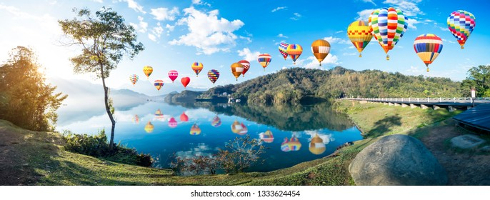 Colorful hot air balloon fly over panorama landscape view of mountain and lake with reflection in the morning under blue sky and white cloud at Sun Moon Lake, Nantou, Taiwan