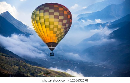Colorful hot air balloon flying over misty mountains - freedm, travel concept