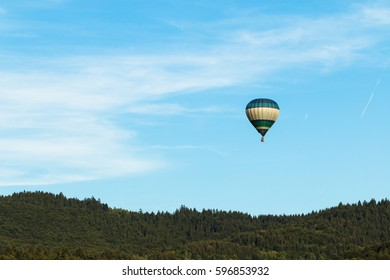 colorful hot air balloon flying and adventure traveling  over green hills on blue sky with some clouds