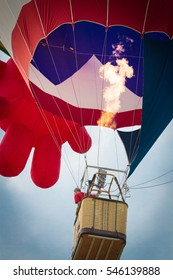 A colorful hot air balloon as it is inflated for flight, burning burner. Concept of preparation. start off a journey/ competition.