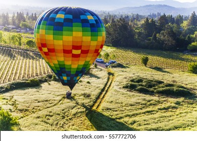 Colorful hot air balloon landing in a field, Napa, California, USA.
