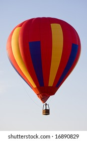 A colorful hot air balloon in mid-air on a clear day with no one on board!  Put your own favorite balloon pilot in the gondola!
