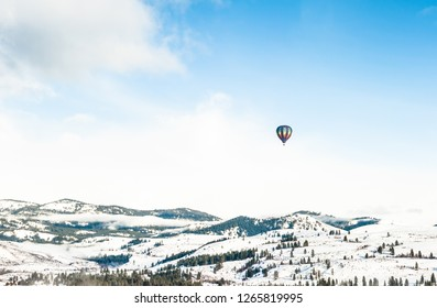Colorful Hot Air Balloon Over the Mountains in Winter