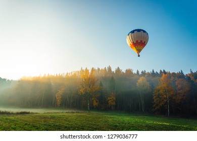 Colorful hot air balloon over the green field. Outdoor activity over national park. Traveling concept