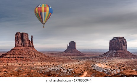 Colorful hot air balloon over majestic monument valley covered in snow