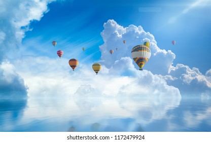 Colorful hot air balloons fly in blue sky with white clouds and bright sun above serene sea