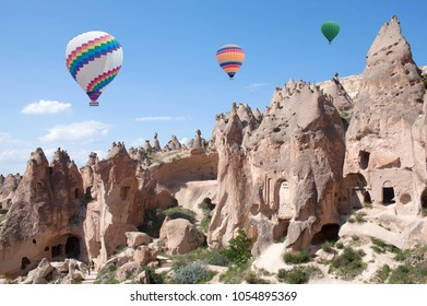 Colorful hot air balloons flying over unique geological formations in Zelve valley, Cappadocia, Central Anatolia, Turkey