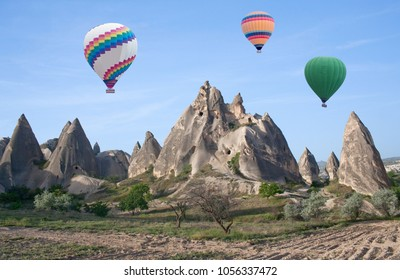 Colorful hot air balloons flying over unique geological formations in Cappadocia, Central Anatolia, Turkey