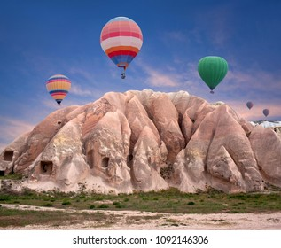 Colorful hot air balloons flying over unique geological formations in Red valley, Cappadocia, Central Anatolia, Turkey