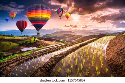 Colorful hot air balloons flying over Terraced Paddy Field in Mae-Jam Village , Chaing mai Province , Thailand.